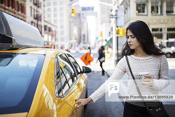Junge Frau öffnet Taxitür auf Stadtstraße