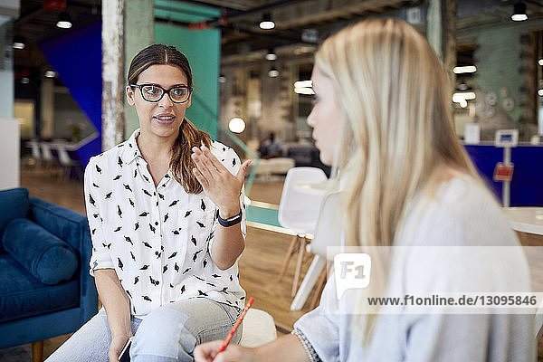 Confident businesswomen planning strategy while sitting at creative office