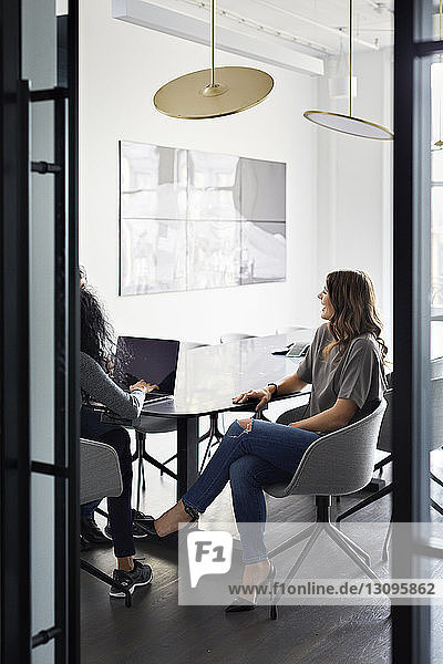 Weibliche Kollegen diskutieren über Laptop-Computer im Konferenzraum mit Blick durch die Tür