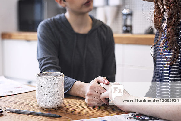 Midsection of lesbian couple holding hands while sitting at dining table