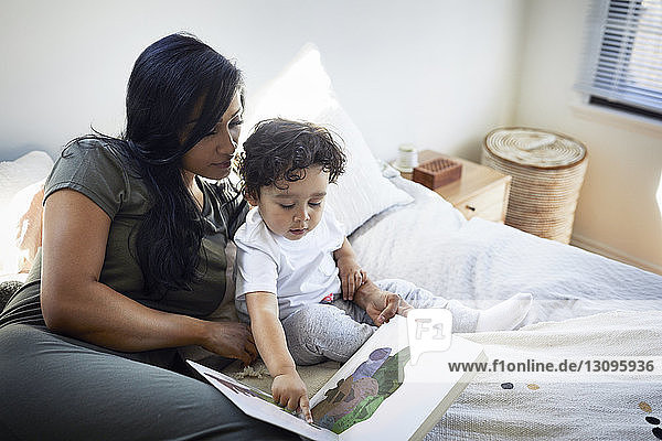 Cute son pointing at picture book while sitting by mother on bed