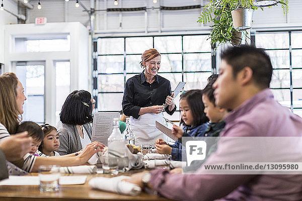 Kellnerin nimmt im Restaurant die Bestellung der Familie entgegen