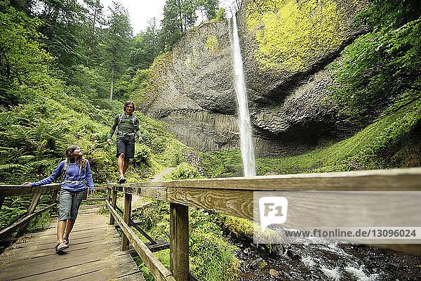 Paar zu Fuss auf Steg am Wasserfall im Wald