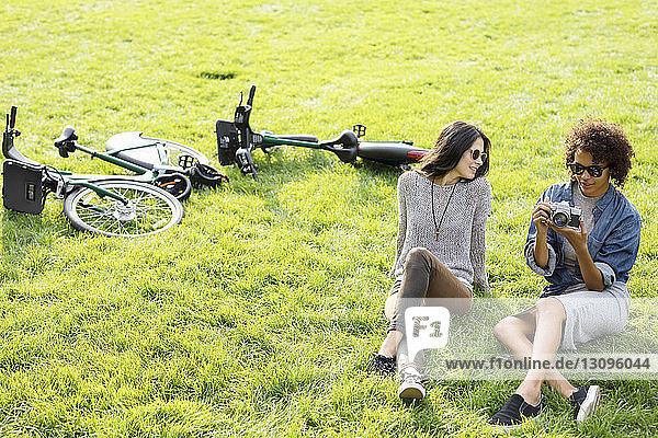 Hochwinkelaufnahme von Freunden mit Kamera  die sich auf einem Grasfeld entspannen
