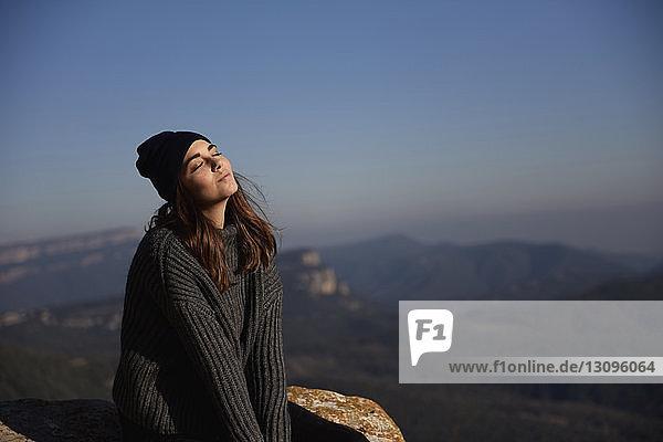 Frau mit geschlossenen Augen auf Klippe gegen den Himmel sitzend