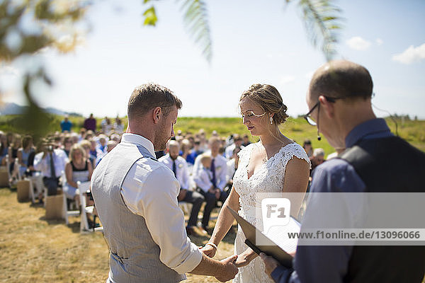 Young couple getting married by priest during sunny day