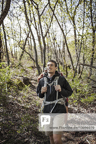 Happy man carrying backpack while hiking in forest