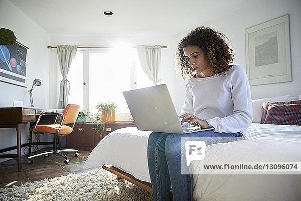 Niedriger Blickwinkel einer Frau  die einen Laptop-Computer benutzt  während sie zu Hause auf dem Bett sitzt