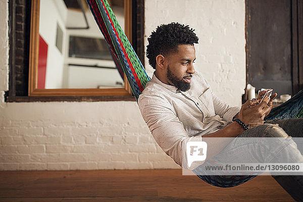 Junger Mann benutzt Smartphone  während er zu Hause auf der Hängematte sitzt
