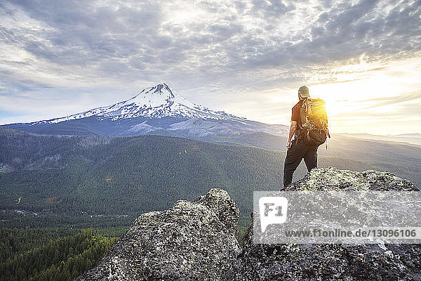 Rückansicht eines Wanderers  der auf dem Berg vor bewölktem Himmel steht