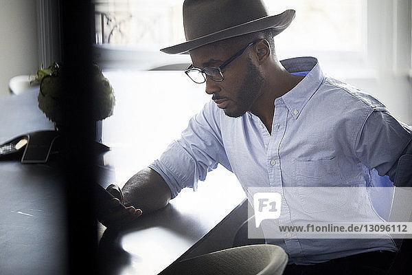 Geschäftsmann benutzt Mobiltelefon,  während er im Konferenzraum sitzt
