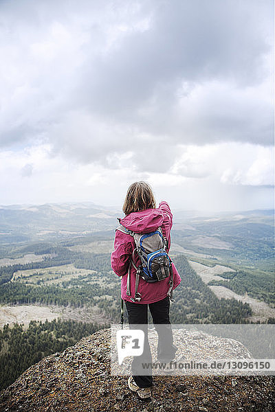 Rear view of woman standing on mountain against cloudy sky