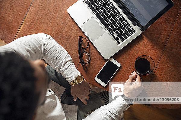Draufsicht auf einen Mann  der schwarzen Kaffee trinkt  während er seinen Laptop am Tisch benutzt