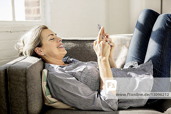 Happy woman using smart phone while lying on sofa at home