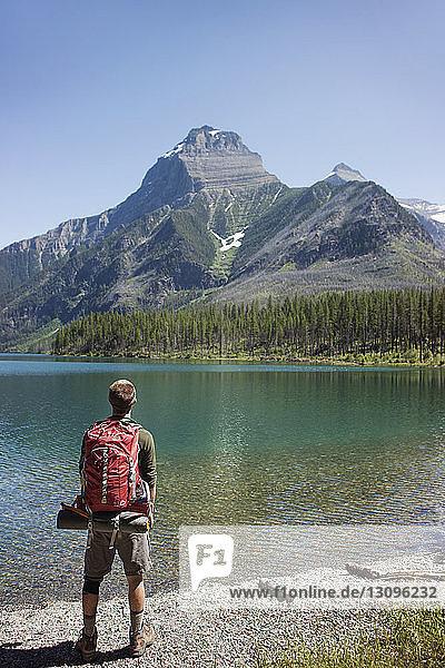 Rückansicht eines am Seeufer stehenden Mannes mit Rucksack im Glacier National Park
