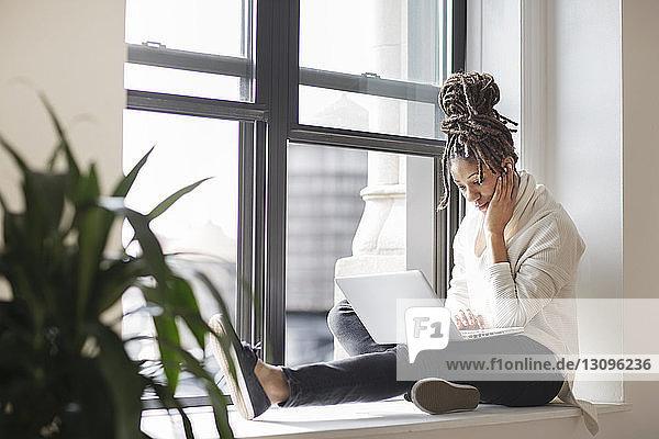 Geschäftsfrau  die mit einem Laptop arbeitet  während sie im Büro am Fenster sitzt