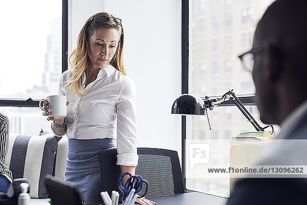 Businesswoman holding coffee cup while standing at office with male colleague in foreground