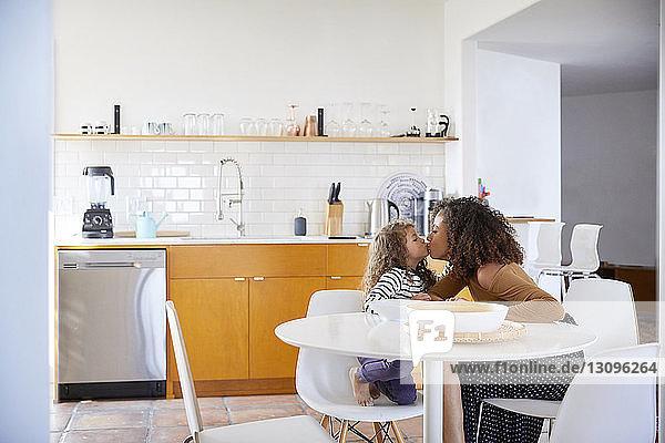 Seitenansicht einer Mutter  die ihre Tochter küsst  während sie zu Hause auf Stühlen sitzt