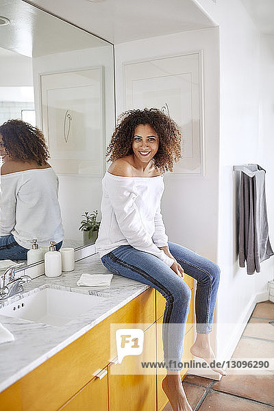 Portrait of happy woman sitting by mirror in bathroom at home