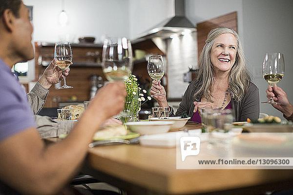 Glückliche Freunde mit Weingläsern sitzen bei geselligem Beisammensein am Tisch