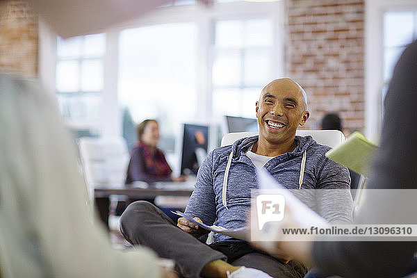Smiling businessman sitting on chair with colleagues at office