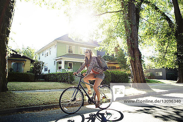 Full length of woman riding bicycle on street during summer