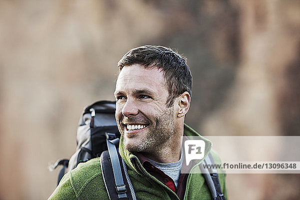 Happy man looking away while hiking on field