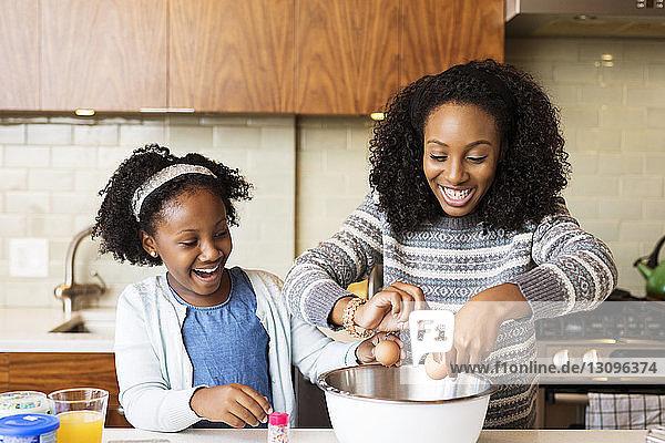 Glückliche Mutter und Tochter backen Cupcakes in der Küche