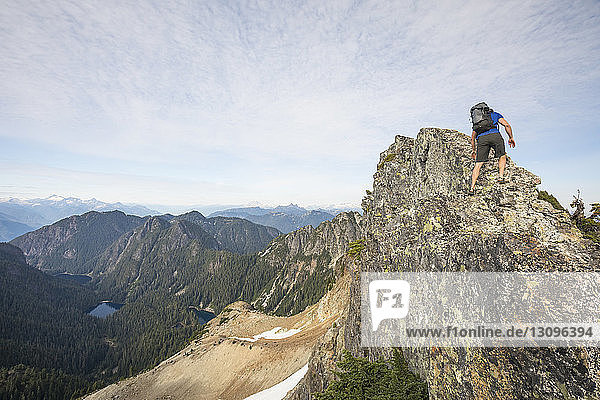 Niedrigwinkelansicht eines Wanderers  der am Berg gegen den Himmel klettert