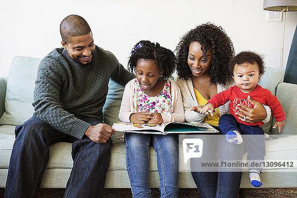 Glückliche Familie schaut ins Bilderbuch  während sie auf dem Sofa sitzt
