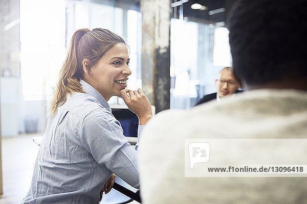 Smiling businesswoman sitting with male colleagues in meeting at office