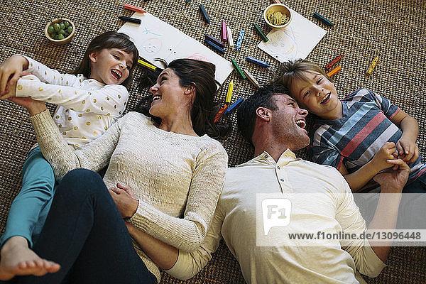 Draufsicht auf glückliche Eltern mit Kindern  die zu Hause auf einem Teppich liegen