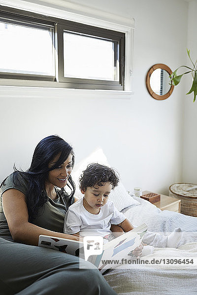 Mother and son looking at picture book while relaxing on bed at home