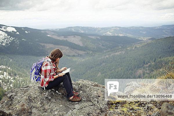 Frau benutzt Tablet-Computer  während sie auf dem Gipfel eines Berges vor bewölktem Himmel sitzt