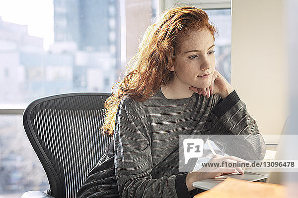Confident woman using laptop computer while sitting by window