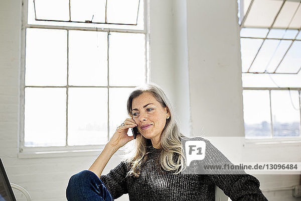 Mature woman talking on mobile phone while sitting against windows at home