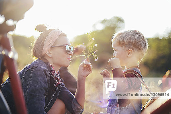 Side view of mother giving flowers to son on field during sunny day