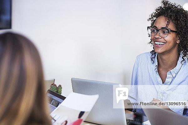 Lächelnde Geschäftsfrau mit Kollegin am Konferenztisch im Sitzungssaal