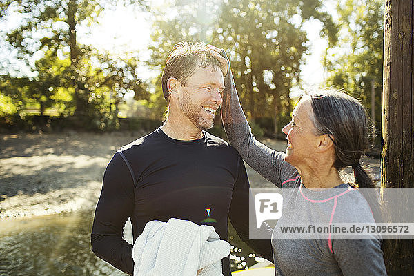 Happy woman pulling man's hair while standing by river