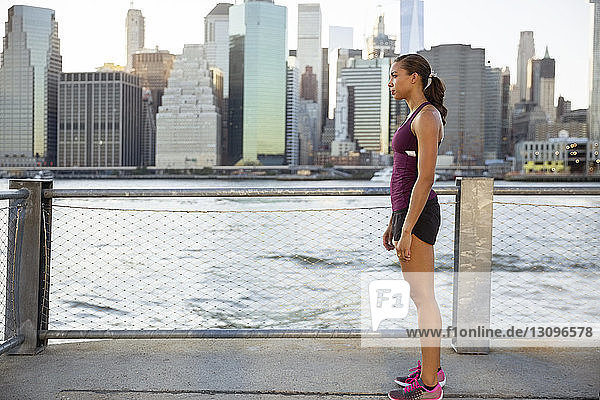 Side view of female athlete standing on promenade by river