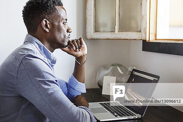 Nachdenklicher Mann schaut weg  während er zu Hause mit einem Laptop-Computer sitzt