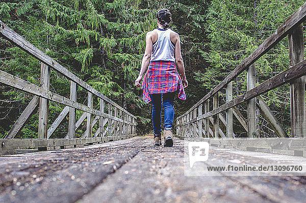 Rear view of woman walking on footbridge amidst trees in forest
