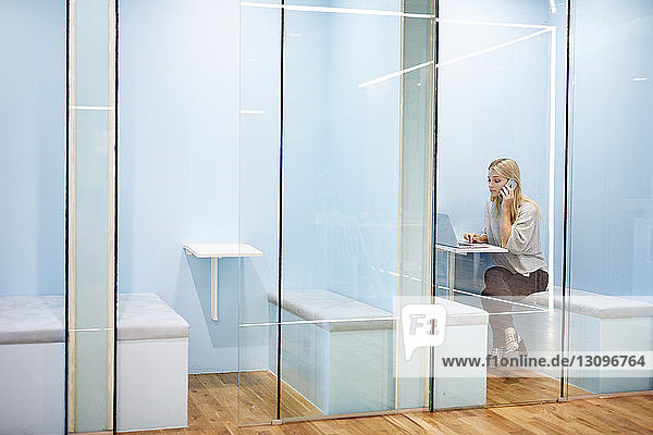 Serious businesswoman talking on mobile phone while using laptop in cubicle at office