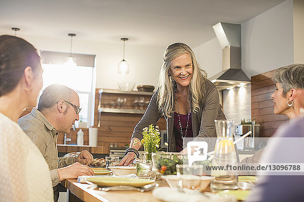 Woman serving food for friends sitting at dining table