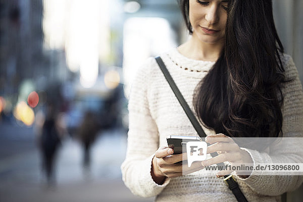 Midsection of young woman using smart phone on city street