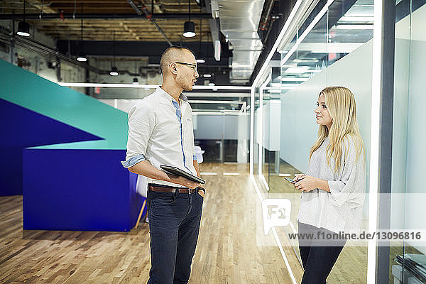 Business colleagues discussing while standing in corridor at office