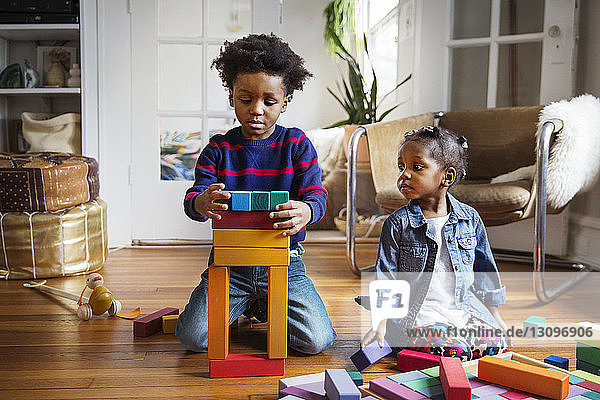 Boy and girl playing with toy blocks at home