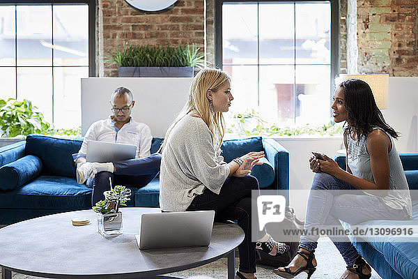 Businesswomen discussing and male colleague working on laptop while sitting at sofa in office