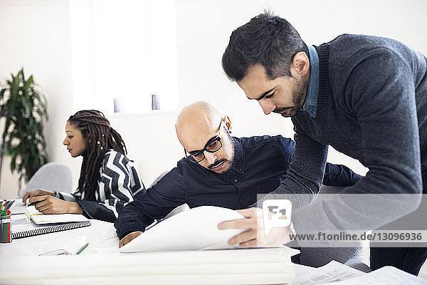 Geschäftsmann zeigt einem männlichen Kollegen Dokumente auf dem Tisch im Büro