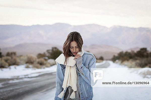 Junge Frau hält Schalldämpfer in der Hand  während sie auf schneebedeckter Straße gegen Berge steht